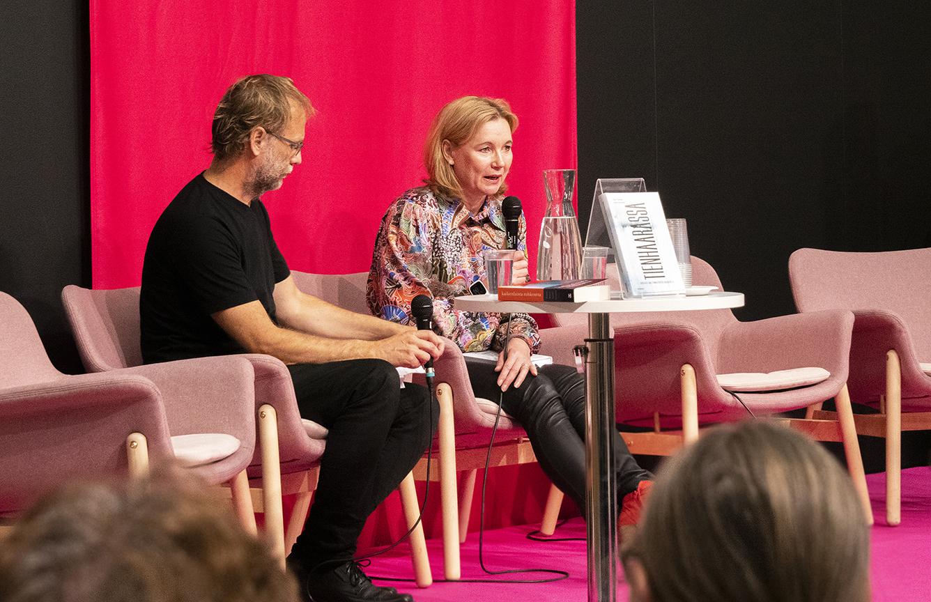 Lavalla on kaksi henkilöä, jotka puhuvat yleisölle.
